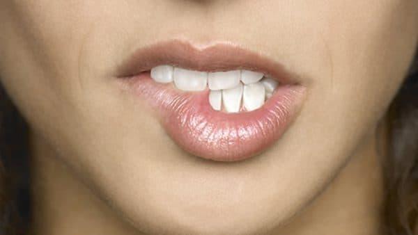 прижать уголки рта к зубам