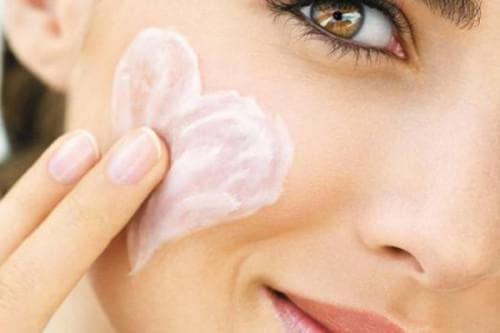 нанесение крема на женское лицо